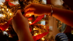 Woman places a bow tie on a Christmas tree around the holidays ALT