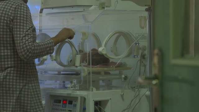 woman places baby in ventilator in baghdad hospital - baghdad stock videos & royalty-free footage