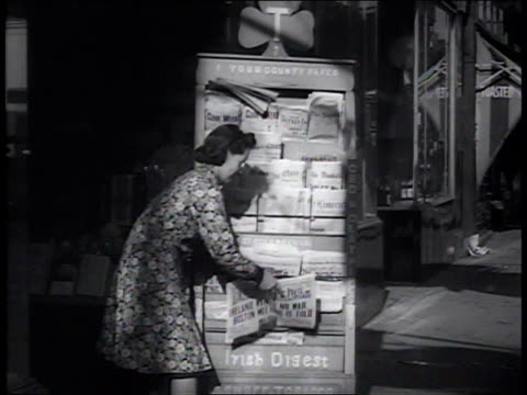 vidéos et rushes de 1941 ws woman places newspaper on a news stand / brooklyn, new york, united states - kiosque à journaux