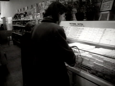 vídeos de stock e filmes b-roll de a woman places packets of butter into her basket in a supermarket - vendas