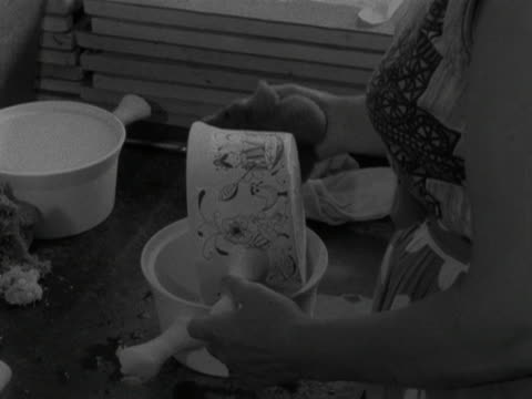 woman places patterned transfers onto a clay saucepan at the stavanger pottery workshop. 1959. - stavanger stock videos & royalty-free footage