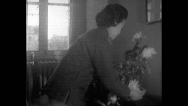 woman places plant on a side table in chinese home; 1964 - maoism stock videos & royalty-free footage