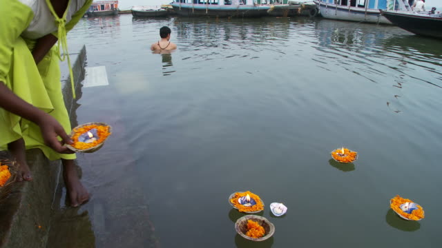 Woman places several floating candles in the water.