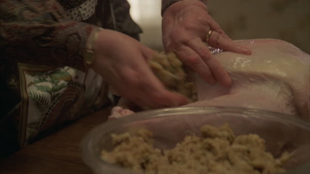 A woman places stuffing in a turkey.