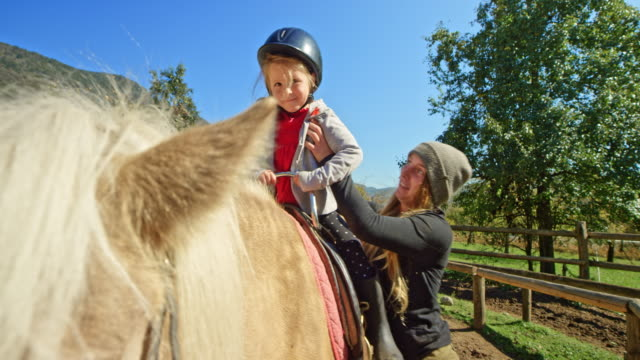 woman placing a little girl on the horse's back in sunshine - horseback riding stock videos & royalty-free footage