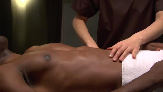 vídeos de stock e filmes b-roll de cu pan woman placing acupuncture needles in man's stomach / new york, usa - acupuntura