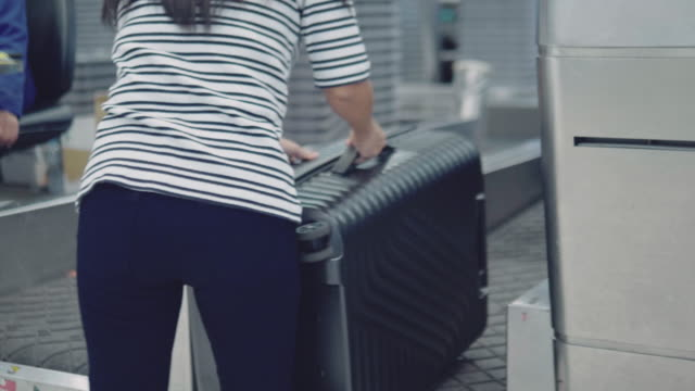 woman placing baggage at check-in counter - luggage stock videos & royalty-free footage