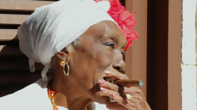 stockvideo's en b-roll-footage met cu woman placing cigarette in her mouth / havana, cuba - alleen oudere vrouwen