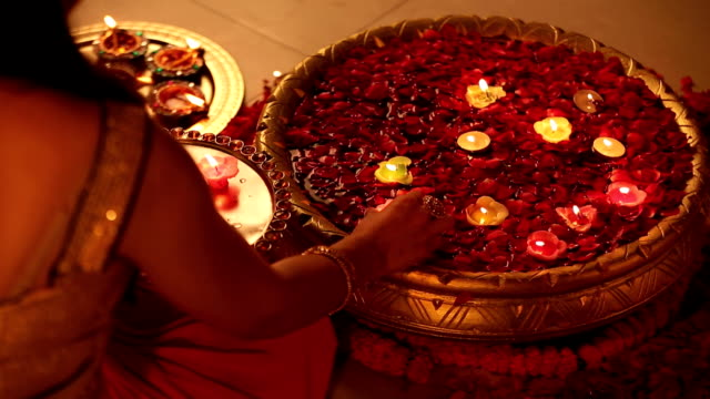ms ha woman placing diyas in bowl during diwali festival at home - oil lamp stock videos & royalty-free footage