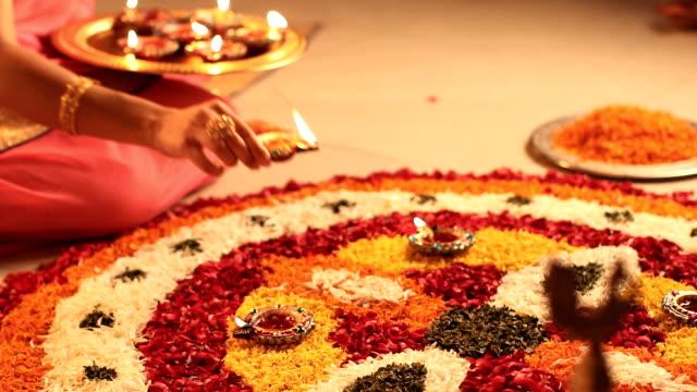 cu ha woman placing diyas on flower rangoli during diwali festival - 盆点の映像素材/bロール