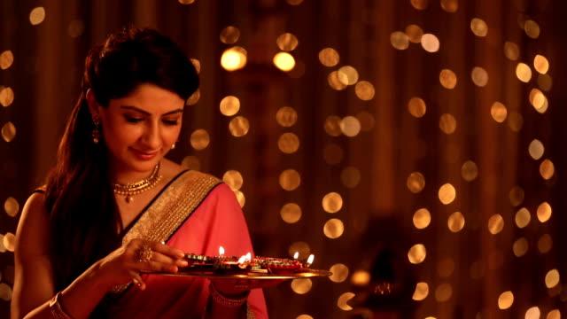 ms woman placing diyas on plate during diwali festival at home - 盆点の映像素材/bロール