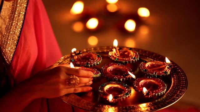 vídeos y material grabado en eventos de stock de cu woman placing diyas on plate during diwali festival at home - bandeja para servir
