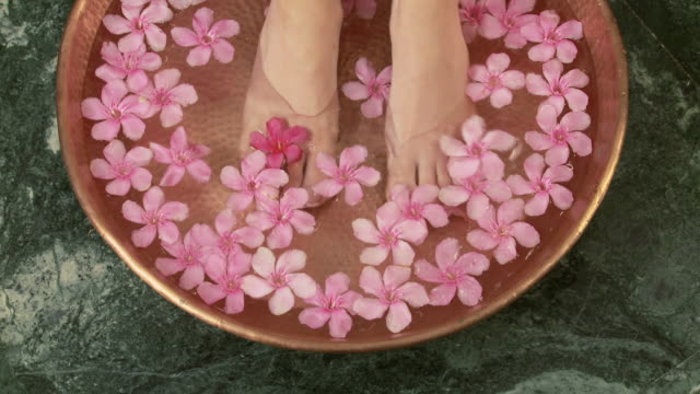 Woman placing feet in bowl of water and flowers