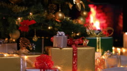 Woman placing gifts under Christmas tree near fireplace