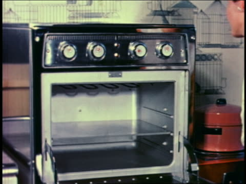 1950 woman placing glass pan with meat into oven + closing door of oven