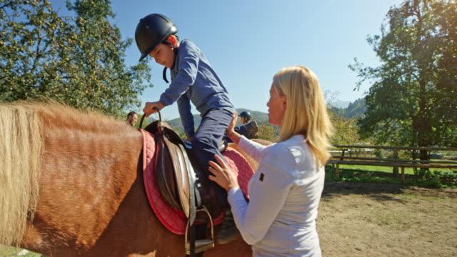 女性日当たりの良いペンで馬に彼女の息子を配置します。 - 乗馬点の映像素材/bロール