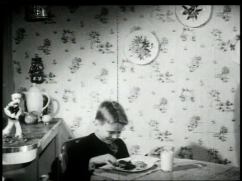 1948 montage woman placing plate of spinach in front of boy / united states - 1948 stock videos & royalty-free footage