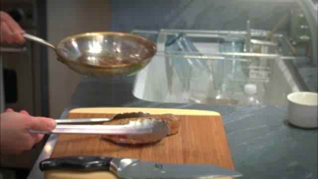 CU Woman placing seared tuna steak on cutting board, New York City, New York, USA