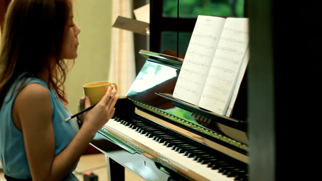 Woman plaing piano and drink coffee