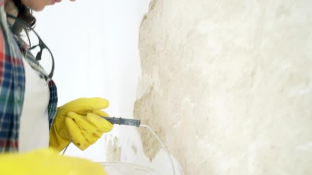 Vrouw pleisteren van de muur met het palet in haar huis.