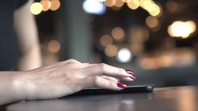 vídeos y material grabado en eventos de stock de mujer jugar móvil en café con espacio de copia naranja - esmalte de uñas rojo