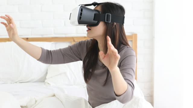 Woman playful Virtual Reality Headset at Home in bedroom