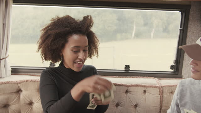woman playing cards with friends in camper van - luck stock videos & royalty-free footage