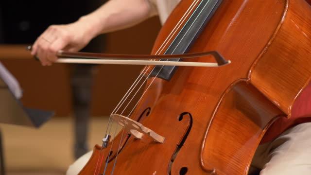 vidéos et rushes de femme jouant le violoncelle au concert classique - violoncelle