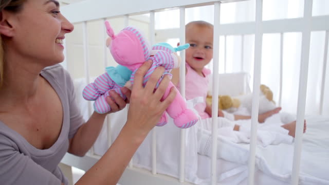 woman playing dolls with her baby - cot stock videos & royalty-free footage