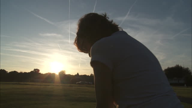 CU Woman playing golf at sunset, Brussels, Belgium