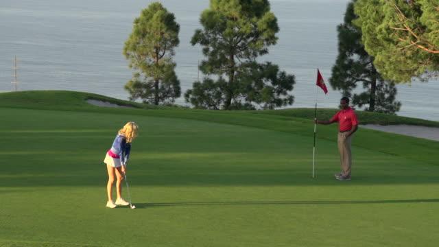 vídeos y material grabado en eventos de stock de a woman playing golf. - slow motion - bandera de golf