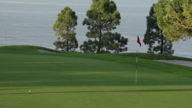 a woman playing golf. - slow motion - bandierina da golf video stock e b–roll