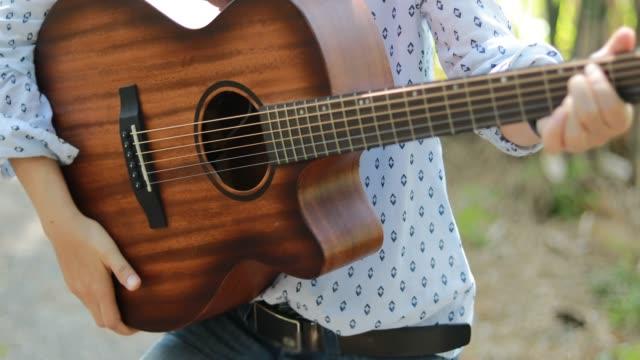 vídeos de stock, filmes e b-roll de mulher que joga a guitarra no tempo do relax - violão acústico