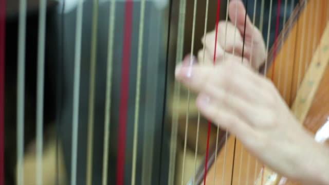 Mujer jugando al arpa en concierto