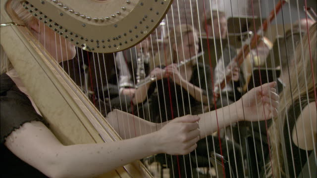 cu woman playing harp in orchestra, musicians in background / london, united kingdom - harp stock videos & royalty-free footage