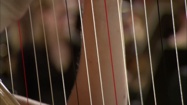 cu woman playing harp in orchestra, violinists in background / london, united kingdom - harp stock videos & royalty-free footage