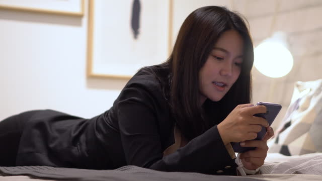 woman playing on smartphone. beat the game and win - online casino stock videos & royalty-free footage