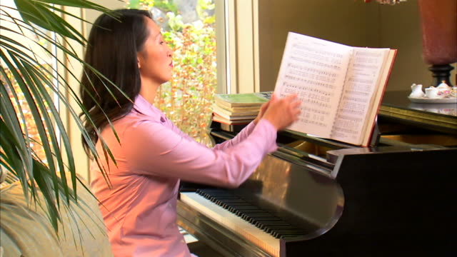 ms woman playing piano at home / salt lake city, utah, usa - solo una donna di età media video stock e b–roll
