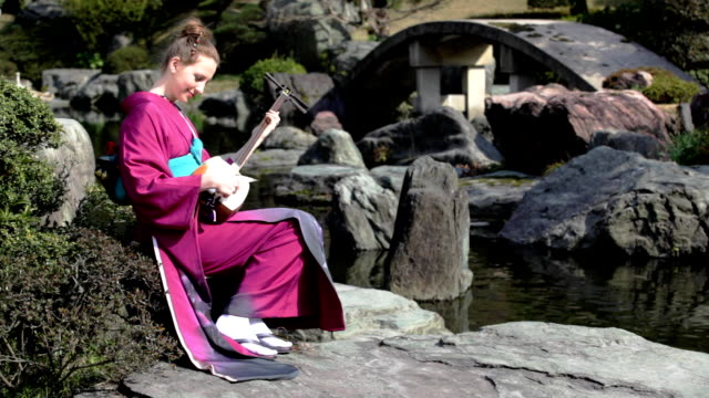 hd: woman playing shamisen in japanese garden (video) - kimono stock videos and b-roll footage