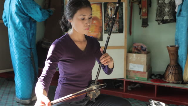 woman playing string instrument called morin khuur - string instrument stock videos and b-roll footage