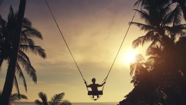 slo mo frau spielen schaukel am strand bei sonnenuntergang - schaukel stock-videos und b-roll-filmmaterial