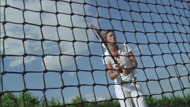 MS, LA, Woman playing tennis seen through net, Chateau du Parc, Saint Ferme, France