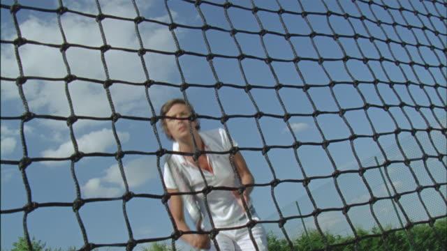 MS, LA, CANTED, Woman playing tennis seen through net, Chateau du Parc, Saint Ferme, France
