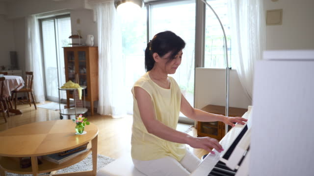 woman playing the piano in living room - piano stock videos & royalty-free footage