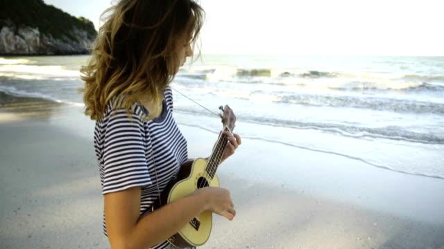 vídeos de stock, filmes e b-roll de mulher tocando cavaquinho, perto do mar - violão acústico