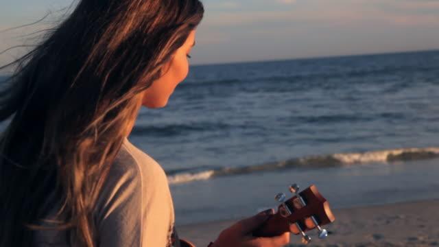 vídeos de stock, filmes e b-roll de woman playing ukulele on beach - ukulele