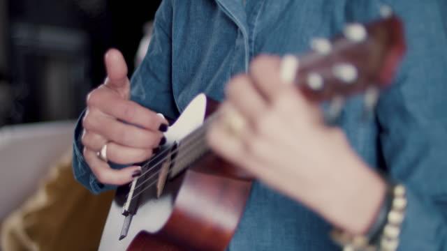 woman playing ukulele - chitarra video stock e b–roll