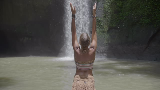 a woman playing under a waterfall in exotic tropical bali, indonesia. - zen like stock videos & royalty-free footage