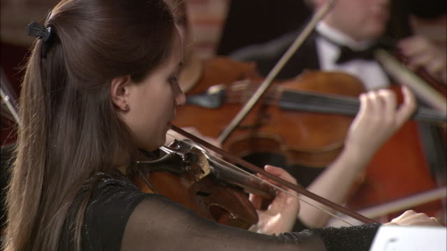 CU Woman playing violin in orchestra, musicians in background / London, United Kingdom