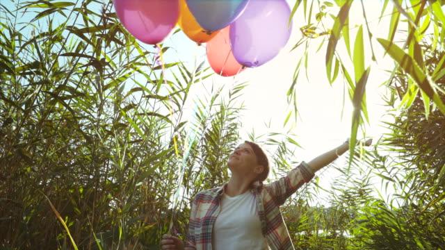 vídeos y material grabado en eventos de stock de mujer jugando con un montón de globos. - manojo